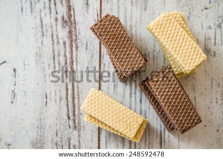 White and black wafer biscuits aligned on white wooden background - stock photo