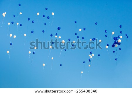 White and blue balloons in the sky - stock photo