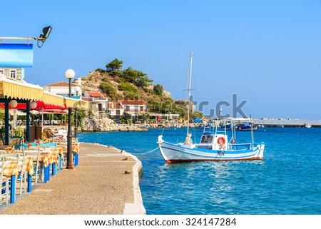 White and blue color Greek fishing boat mooring in Kokkari port, Samos island, Greece - stock photo
