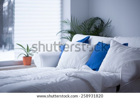 White and blue cushions on the bed - stock photo