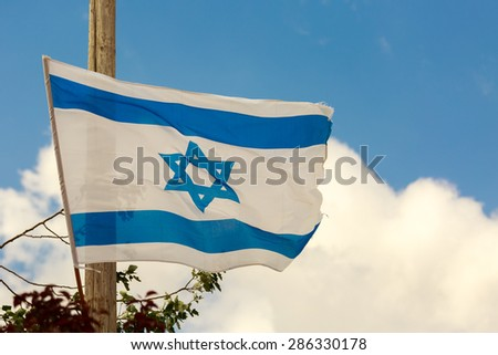 White and blue flag of Israel waving in the wind over the clouds in sky - stock photo