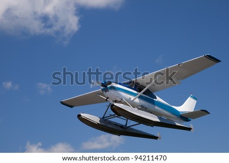 White and blue float plane against cloudy sky