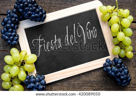 "white and blue grapes with a slate on wooden table, spanish text ""fiesta del vino ""on it, which means wine festival"