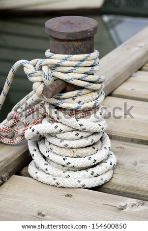 White and blue rope knotted around a ship bollard - stock photo