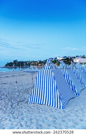 White and blue tents on the beach at sunset.
