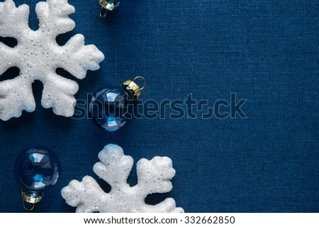 White and blue xmas ornaments on blue canvas background. Merry christmas card. Winter holidays. Xmas theme. Happy New Year. - stock photo