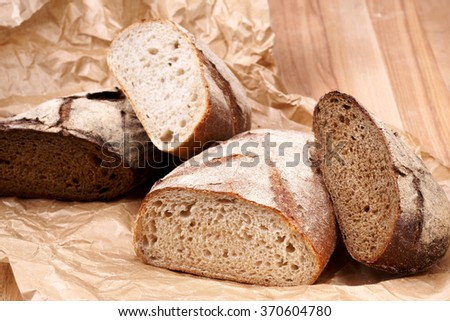 White and brown bread on backers paper and wooden table