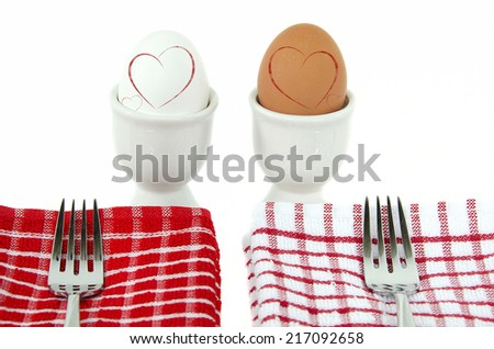white and brown hard boiled eggs in cups with red hearts and forks on checkered napkin - stock photo