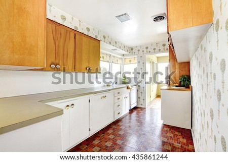 White and brown kitchen interior with tile and floral patterned wall paper - stock photo