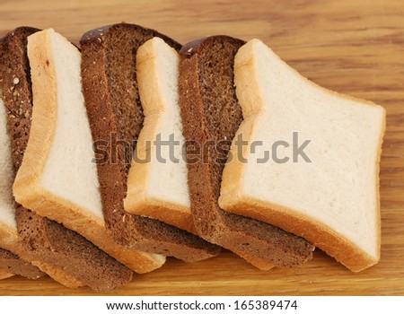 White and brown loaf of bread on wooden table. Whole background.
