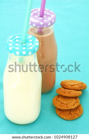 White and chocolate milk in glass bottles with ginger cookies in vertical format and shot in natural light