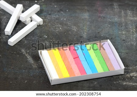 White and colored chalks on the old blackboard - stock photo