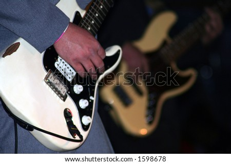 White and cream-colored guitars being played.