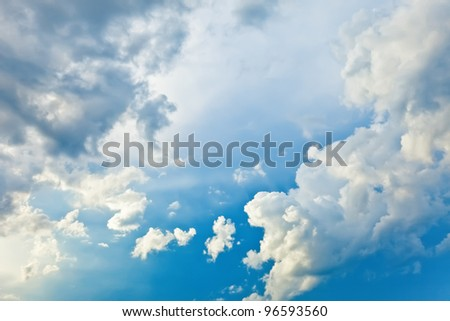 white and dark cumulus clouds against a bright blue sky without the sun - stock photo