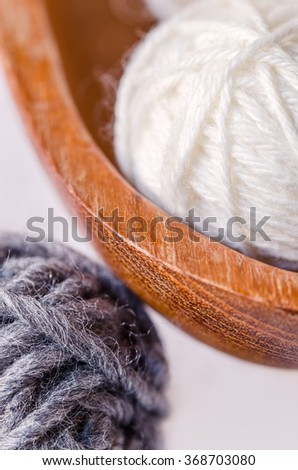 White and gray ball of wool in a wooden dish. Close up. - stock photo