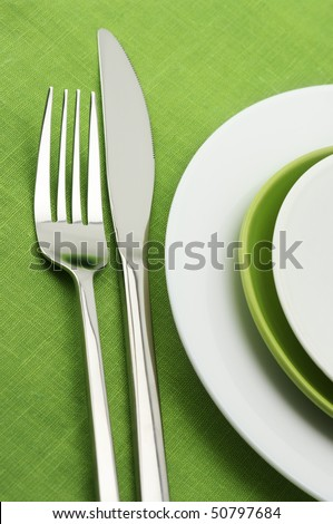 White and green plates, stainless fork and knife on green linen tablecloth.