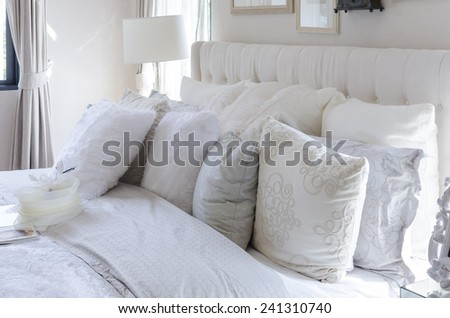 white and grey pillows on bed in luxury bedroom - stock photo