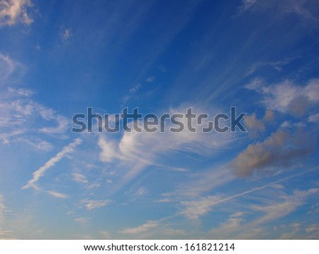 White and grey wispy clouds in a blue sky. - stock photo