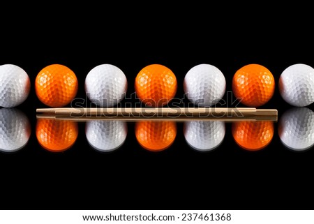 White and orange golf balls with bamboo chopsticks on the glass  table