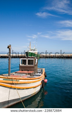 White and orange old fishing boat in the harbour of kalkbay against a blue clear sky and the ocean. Cape Twon -  South Africa - stock photo