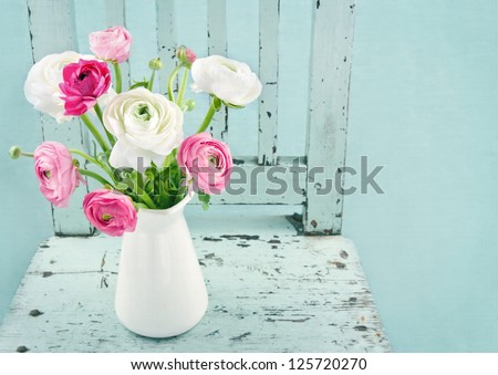 White and pink flowers on light blue vintage chair - stock photo