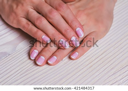 White and pink nail art on the wooden background