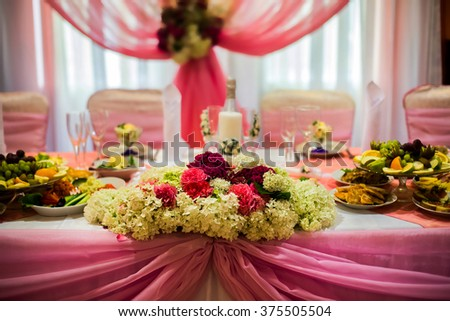 white and purple flowers, wedding accessories, wedding preparation, decorated wedding table with flowers, wedding flowers, food on the table,  decorated chairs,glasses, fruit grapes salad on the table - stock photo