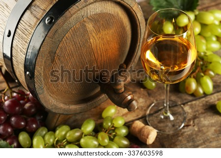 White and red grape with wine bottle near barrel on wooden background - stock photo
