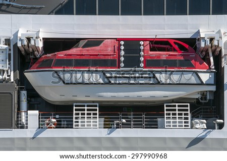 White and red life boat of a big modern cruise liner in the ocean - stock photo