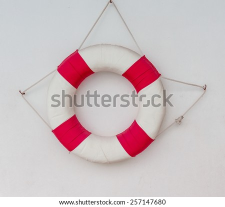 white and red  lifebuoy on white wall, float on the wall - stock photo