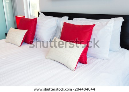 White and red pillows on a bed Comfortable soft pillows on the bed - stock photo