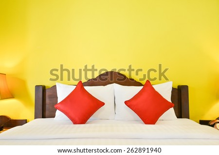 White and red pillows on comfortable bed - stock photo