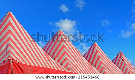 white and red tents under a blue sky - stock photo