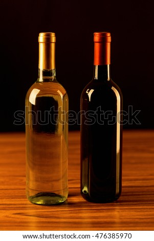 White and red wine bottles on wooden table and black background