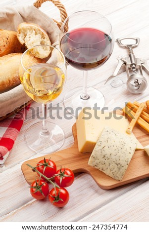 White and red wine glasses, cheese and bread on white wooden table background - stock photo