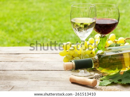 White and red wine glasses, wine bottle and white grape on wood table with copy space - stock photo