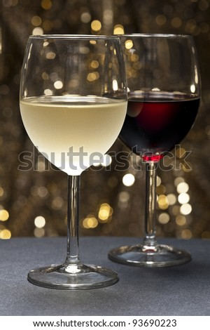 White and Red Wine in front of beautiful gold glitter background - stock photo