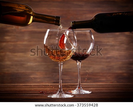 White and red wine pouring in glasses on wooden background - stock photo