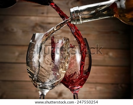 White and red wine pouring on wood background - stock photo