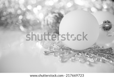 White and silver xmas ornaments on bright holiday background