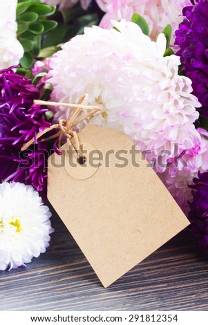 white and violet aster flowers on table with empty paper tag - stock photo