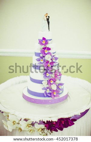 White and violet wedding cake stands on the white table decorated with orchids - stock photo