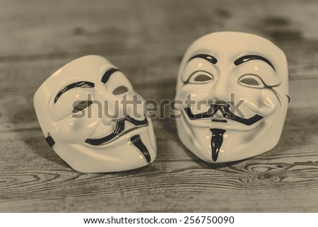 white and yellow anonymous masks on wood background - retro style - stock photo