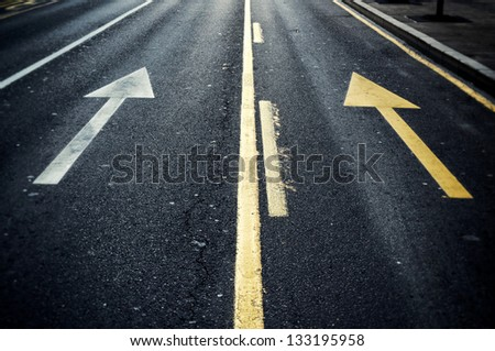 White and yellow arrows on the street - stock photo