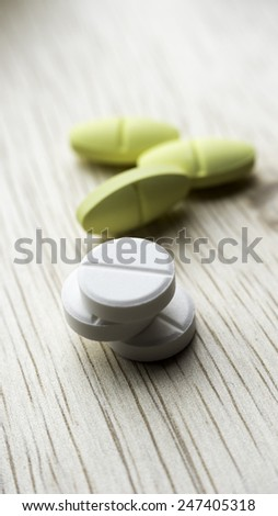 White and yellow pills on table. Copy space. Slightly defocused and closeup shot. - stock photo