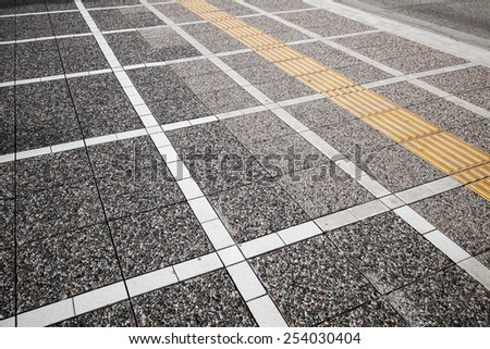 White and yellow road marking lines over on gray cobblestone pavement, abstract urban background pattern - stock photo