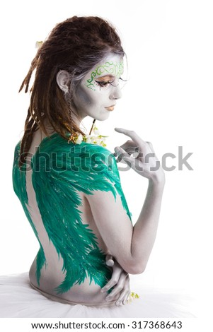 White angel bodypaint model with green wings painted on her back, wearing ballet skirt. Isolated on white background.