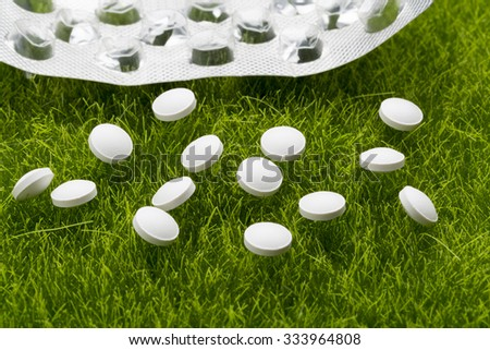 White antibiotic pills and empty blister pack scattered on the green grass