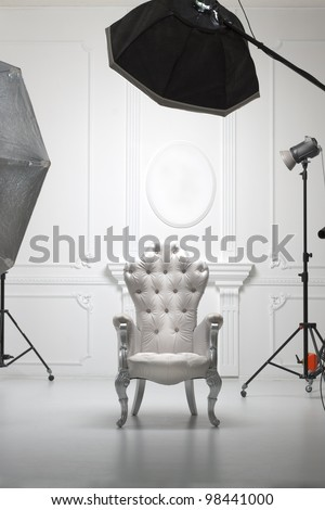 White antique chair in photographic studio with modern lighting equipment - stock photo