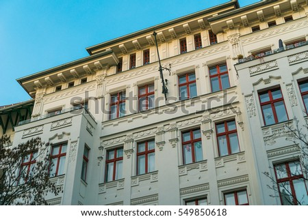 white apartment building with red windows